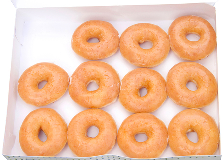 Top view flat lay of plain glazed donuts in a white box isolated. One dozen minus one donut. The original glazed donut has remained peoples favorite throughout history.