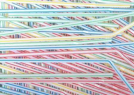 Top view flat lay of colorful striped plastic straws. California just became the first US state to ban plastic straws in restaurants, unless customers ask for one. Stock Photo