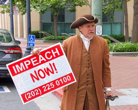 Oakland, CA - June 15, 2019: Unidentified protesters with signs in front of the Federal Courthouse, demanding an inquiry into the impeachment of Donald Trump