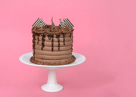 Close up on whole chocolate cake with chocolate ganache dripping down the sides and candy garnish on top presented on small off white porcelain plate pedestal, pink background with copy space