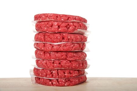 Stack of raw hamburger meat patties on a wood table with pieces of parchment paper between the burgers to prevent them from sticking. Isolated on white background.