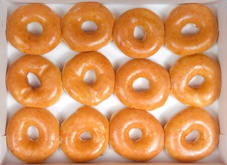 Top view flat lay of plain glazed donuts in a white box isolated. One dozen donuts. The original glazed donut has remained peoples favorite throughout history. Imagens