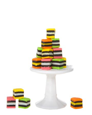 Colorful fancy candy licorice squares piled on a tiny pedestal with several at the base of it isolated on white. Perfect for party.