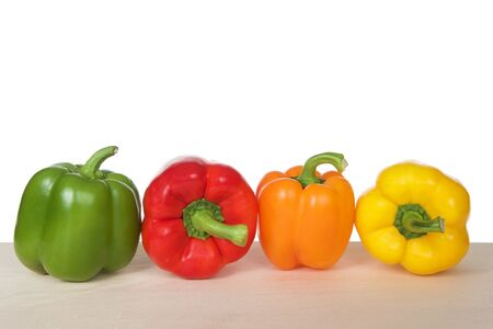 Bell Peppers on a wood table isolated on white. Green, red, orange and yellow varieties. Like the tomato, bell peppers are botanical fruits but culinary vegetables. Reklamní fotografie