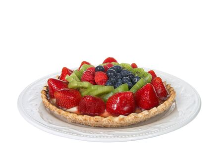 Fresh fruit tart on a pastry crust coated with chocolate on a white plate isolated on white background. Focus stacked for deeper depth of field. Reklamní fotografie