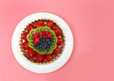 Fresh summer fruit tart with strawberries, kiwi, blueberries, raspberries on a white porcelain plate with pink background. Top view flat lay.