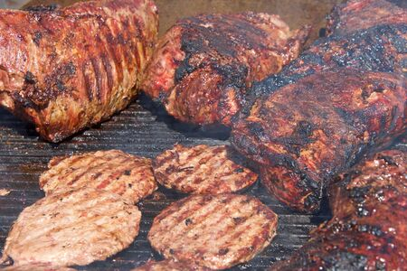 Beef brisket and hamburgers cooking side by side on an open bbq grill. traditional street fair food.