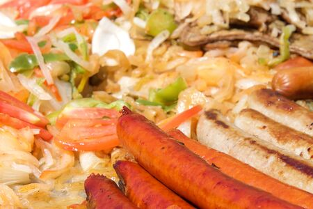 Hot dogs and sausages with onions, jalapenos, and several varieties of bell peppers and tomatoes grilling on an outdoor vendors grill. Close up. Reklamní fotografie