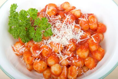 Top view white bowl with green ring around edge with fresh homemade gnocchi covered in marinara sauce and garnished with fresh grated parmesan cheese and fresh home grown parsley. Close up