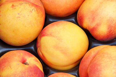 top view flat lay close up of red july yellow nectarines at Farmers market.