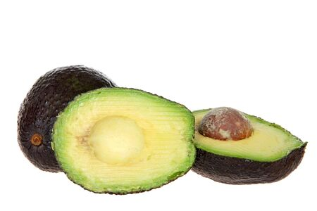 whole avocado and one cut with seed exposed, isolated on white background. Avocados are grown commercially in parts of Florida, California and Hawaii. Reklamní fotografie