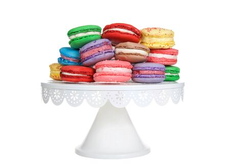 Close up on Macaron cookies in various spring colors stacked on a white pedestal isolated on white background. Popular French treat. Archivio Fotografico - 141063228