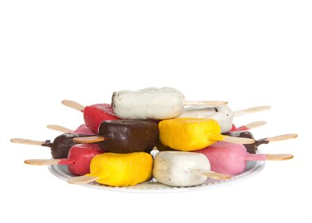 Assortment of colorful cake pop in various flavors and colors on an off white porcelain plate stacked, isolated on white.