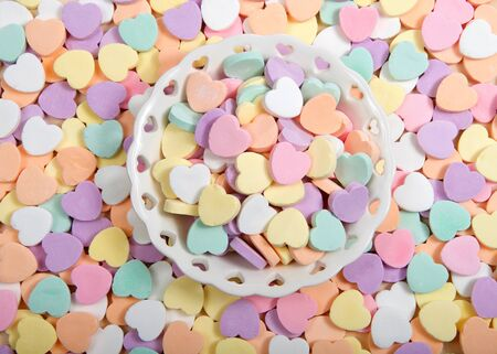 Flat lay top view of a small Porcelain bowl with heart cutouts holding pile of large pastel candy hearts surrounded by more candy. Traditional Valentine's Day candy. no messages on candy. Archivio Fotografico