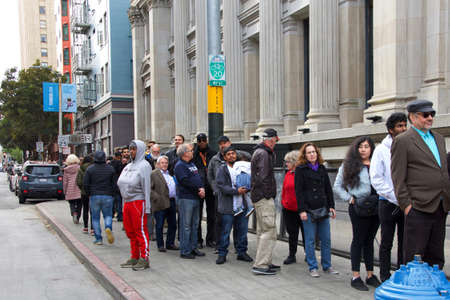 San Francisco, CA - Feb 29, 2020: Unidentified people lined up outside The Hibernia Bank building to hear Presidential candidate Tulsi Gabbard speak at a Town Hall meeting.