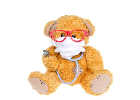 Little fluffy brown bear wearing a white face mask, pink glasses, holding a bear sized stethoscope looking at viewer, Isolated on white.