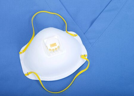 Top view flat lay of one N95 medical grade mask laying on scrub top uniform.