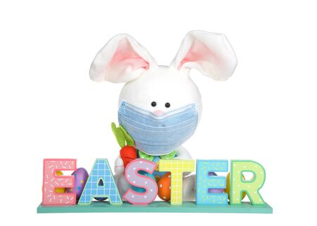 Easter bunny stuffed toy wearing a surgical medical face mask sitting behind a colorful wood block EASTER sign, isolated on white.