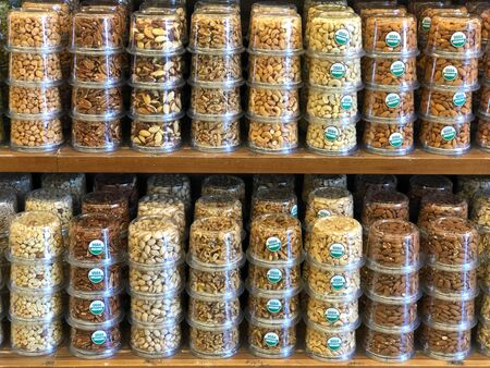 Shelf with rows of nuts stacked for sale. Stickers saying USDA organic. Individually packaged to ensure safety from contamination.