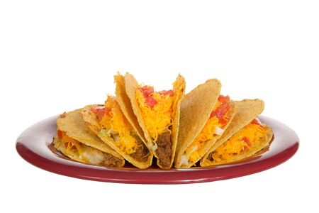 Five crispy tacos on a red plate isolated on white. Popular Americanized Mexican food.
