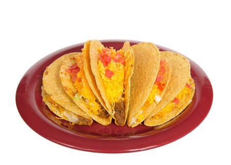 Five crispy tacos on a red plate isolated on white. Popular Americanized Mexican food. Viewed from above at an angle. Archivio Fotografico