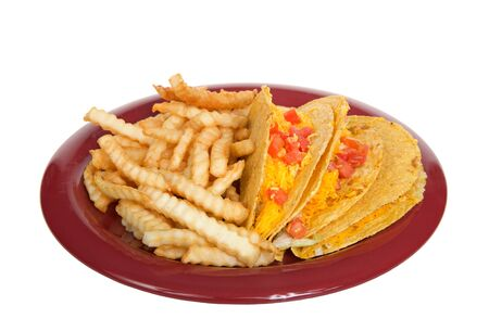 Three crispy tacos on a red plate with french fries, isolated on white. Popular Americanized Mexican food.