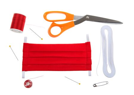 Top view flat lay of hand make surgical style face mask with bright red cotton fabric. Supplies elastic, thread, bobbin, pins, scissors and safety pin to thread elastic.