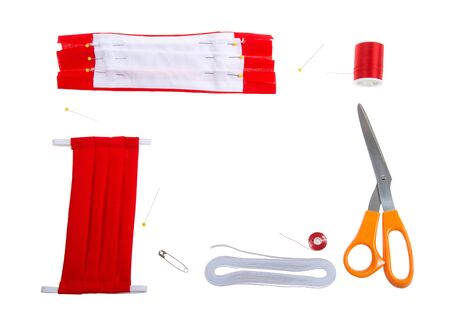 Top view flat lay of hand make surgical style face mask with bright red cotton fabric. Supplies elastic, thread, bobbin, pins, scissors and safety pin to thread elastic. Archivio Fotografico