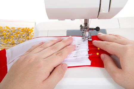Close up of hands make surgical style face mask with filter pocket out of bright red and white cotton fabrics on a well used sewing machine. Isolated on white.
