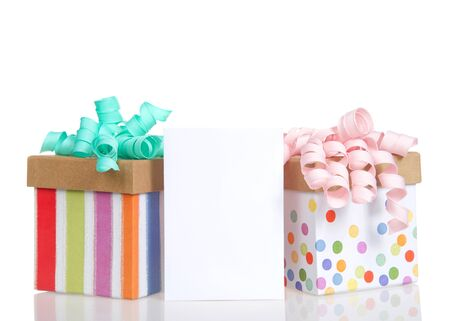 Two colorful festive present boxes with curly bows in pastel pink and turquoise with a blank card for copy space in between. Isolated on white. Archivio Fotografico