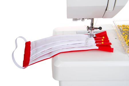 Close up of sewing machine with surgical style face mask with filter pocket being made out of bright red and white cotton fabrics on a well used sewing machine. Isolated on white. Archivio Fotografico