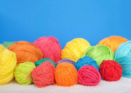 Many bright colorful balls of yarn laying on a blanket, bright blue background with copy space.