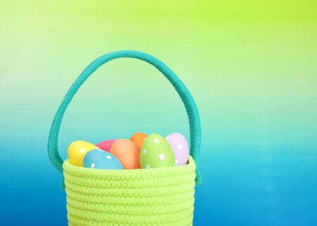 Close up on a bright green yarn woven Easter basket with light blue handle filled with festive colored eggs with dots, Graded background blue base to green above. Archivio Fotografico