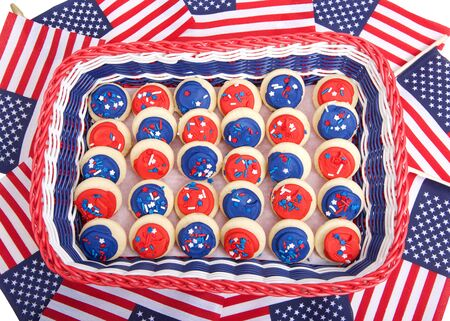 Patriotic basket in red, white and blue filled with bite sized sugar cookies frosted in red and blue frosting covered with stars and sprinkles candies on background of miniature American flags.