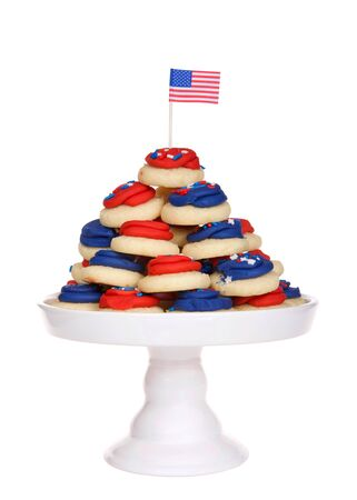 Close up of white porcelain pedestal with vibrant colorful patriotic bite sized frosted sugar cookies with tiny American flag on top. Isolated on white.