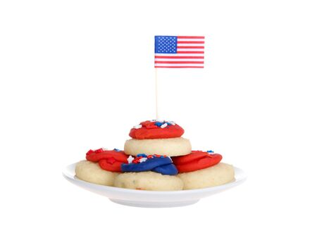 small white porcelain plate with vibrant colorful patriotic bite sized frosted sugar cookies, tiny flag in top cookie. isolated on white Archivio Fotografico