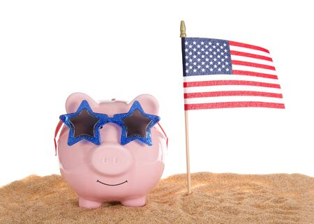 Traditional pink piggy bank wearing star glasses sitting in sand with American Flag waving, isolated on white.