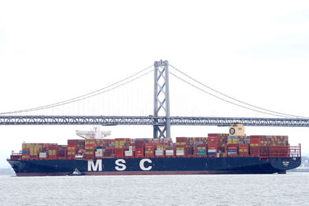 Oakland, CA - Apr 16, 2020: Cargo Ship MSC ANNA, the largest ship to ever dock at the Port of Oakland, passing under the Bay Bridge in route to the port.