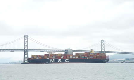 San Francisco, CA - Apr 16, 2020: MSC ANNA, the largest container ship to ever dock at the Port of Oakland, in the San Francisco Bay en route to the port. Passing under the Bay Bridge.