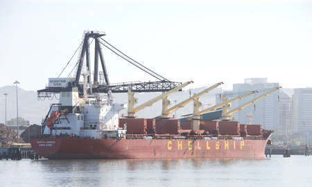 Oakland, CA - May 7, 2020: Bulk Carrier DARYA JAMUNA loading at the Port of Oakland. Schnitzer Steel recycles scrap metal into finished steel products such as rebar and wire rod.