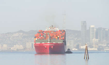 Oakland, CA - May 5, 2020: ONE HARBOUR manuever into the Port of Oakland on a hazy day. Ocean Network Express is a joint venture between Nippon Yusen Kaisha , Mitsui O.S.K. Lines and K Line.