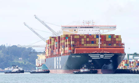 Oakland, CA - Apr 16, 2020: Multiple tugboats working in tandem assist cargo ship MSC ANNA to dock at the Port of Oakland. MSC ANNA is the largest cargo ship to dock at the port.