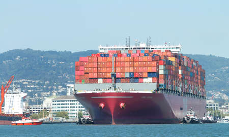 Oakland, CA - July 23, 2020: Pilot vessel GOLDEN GATE approaching Cargo Ship ONE STORK to pick up the harbor pilot as the cargo ship maneuvers to the docks at the Port of Oakland.