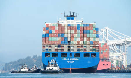 Oakland, CA - July 25, 2020: Cargo Ship COSCO AMERICA maneuvering into the Port of Oakland, the fifth busiest port in the United States.