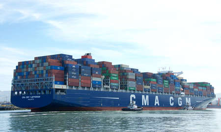Oakland, CA - June 10, 2020: Tugboats assisting cargo ship CMA CGM T. JEFFERSON to maneuver into the Port of Oakland, the fifth busiest port in the United States.