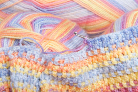 Close up on skeins of multi-colored yarn with partially completed crochet project with hook Zdjęcie Seryjne