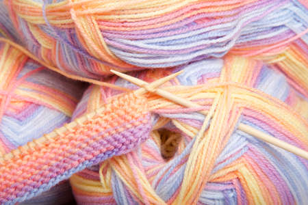 Close up on skeins of multi-colored yarn with partially completed knitting project on natural wood needles.