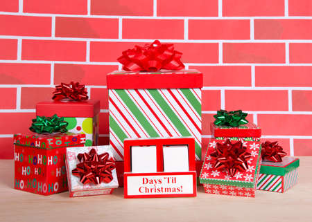 How many days til Christmas white wood blocks in a red box with presents stacked around it sitting on a light wood table with cartoonish brick wall background. Count down blocks blank to fill in days.
