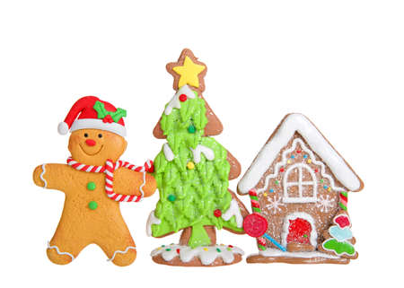 Christmas cookies in a row, isolated on white. Gingerbread man wearing a santa hat and scarf, Christmas tree and decorated gingerbread house. Imagens