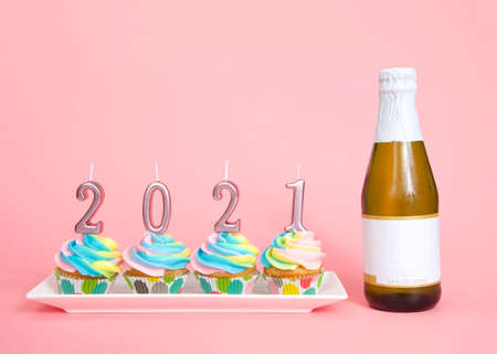 Colorful rainbow frosted vanilla cupcakes sitting in a row on a white, rectagular porcelain plate with 2021 candles on top next to a small bottle of wine, blank label. Pink background Imagens